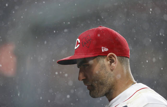Cincinnati Reds first baseman Joey Votto heads into the dugout during a rain delay in the eighth inning of the team's baseball game against the Los Angeles Angels, Tuesday, Aug. 6, 2019, in Cincinnati. On Votto's hat is a heart with the word Dayton written inside. Votto played minor league ball in Dayton. (AP Photo/Gary Landers)