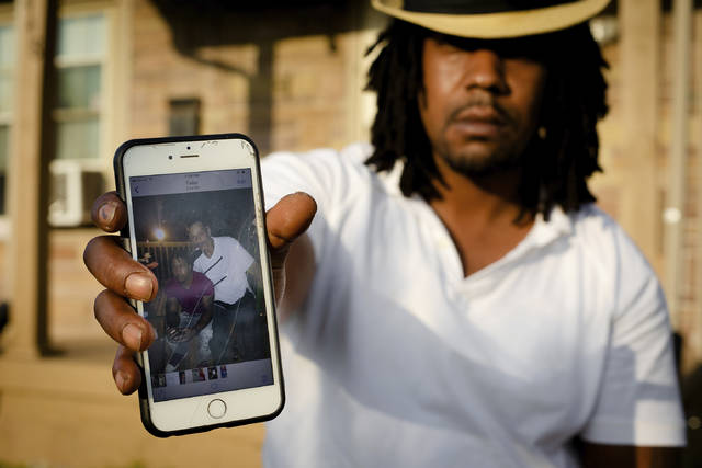 Dion Green holds a cell phone showing a picture of himself and his father, Derrick Fudge,  who was killed in Sunday's mass shooting in Dayton, Ohio, at his home on Tuesday, Aug. 6, 2019 in Dayton.  Green just wanted to have some fun with his family in downtown Dayton after what had been a tough couple of months in the aftermath of damaging tornadoes. But his Saturday night out ended tragically, with his father dying in his arms, his eyes looking into his as he took his final breath. (AP Photo/Robert Bumsted)