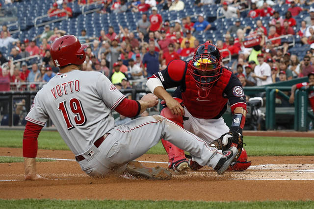 Cincinnati Reds' Joey Votto (19) is out at the plate on a tag by Washington Nationals catcher Kurt Suzuki, right, during the first inning of a baseball game at Nationals Park, Monday, Aug. 12, 2019, in Washington. (AP Photo/Alex Brandon)
