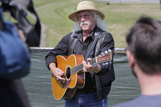 Arlo Guthrie sings as Woodstock fans flock to concert site