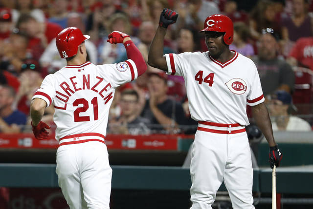 Cincinnati Reds' Michael Lorenzen (21) is congratulated by Aristides Aquino after scoring during the seventh inning of the team's baseball game against the St. Louis Cardinals, Saturday, Aug. 17, 2019, in Cincinnati. (AP Photo/Gary Landers)