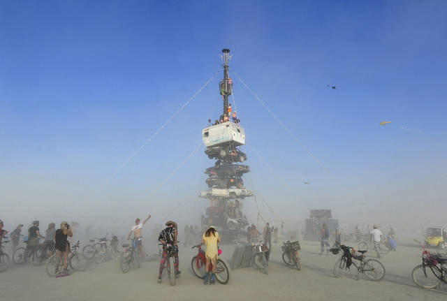 "FILE -  this Monday, Aug. 27, 2018 file photo, burners surrounded by playa dust climb onto an art installation titled, ""Night of the Climb,"" at Burning Man, in Gerlach, Nev. Experts say playa dust doesn't pose any significant health risk to those who inhale it during the annual counter-culture festival in the desert. (Andy Barron/The Reno Gazette-Journal via AP, File)"