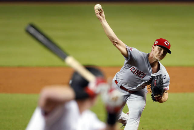 Cincinnati Reds' Sonny Gray, right, pitches to Miami Marlins' Garrett Cooper during the first inning of a baseball game Monday, Aug. 26, 2019, in Miami. (AP Photo/Wilfredo Lee)