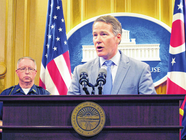 Preble County Sheriff Michael Simpson, left, listens as Ohio Lt. Gov. Jon Husted discusses a proposal to require adding certain warrants to state and federal background check systems during a news conference Wednesday in Columbus.