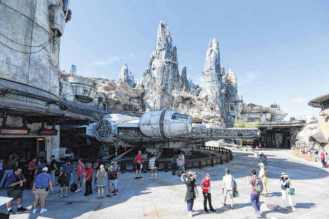 Park visitors walk near the entrance to the Millennium Falcon Smugglers Run ride Tuesday during a preview of the Star Wars-themed land, Galaxy's Edge, in Hollywood Studios at Disney World in Lake Buena Vista, Fla. Anticipated to make landfall in Florida early next week, Hurricane Dorian couldn't come at a more inopportune time for Disney World, which on any given day can host more than 300,000 visitors. The theme park just opened its most anticipated land in decades.