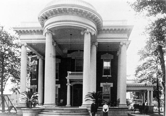 The Russells photographed with their home in 1905. The residence was donated to the YWCA.