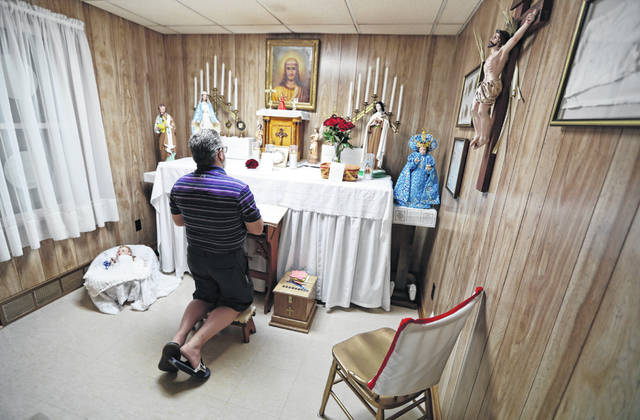 In this Aug. 9, 2019, photo Ron Sattler kneels and prays in front of the altar in Canton, Ohio. Late in the summer of 1939, crowds of strangers started showing up at Rhoda Wise's house next to a city dump in Ohio after she let it be known that miracles were occurring in her room. Eight decades later, people still make pilgrimages to the wood frame bungalow at the edge of Canton, seeking their own miracles.