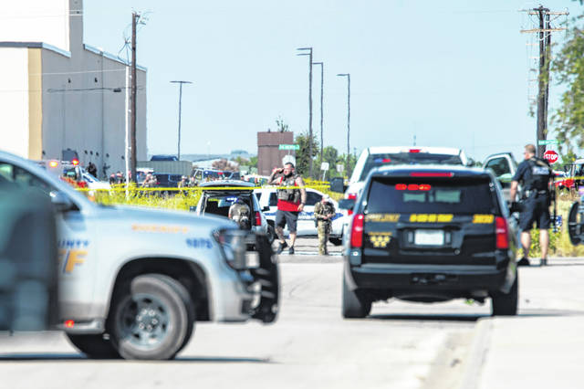 """Odessa and Midland police and sheriff's deputies surround the area behind Cinergy in Odessa, Texas, Saturday, Aug. 31, 2019, after reports of shootings. Police said there are """"multiple gunshot victims"""" in West Texas after reports of gunfire on Saturday in the area of Midland and Odessa."""