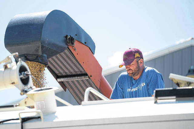 Brent Fuchs fills soybean seed into the trailer of Connie Cihak, who was eager to plant her fields after having had to wait so long because of wet conditions, on June 10 in Dundas, Minn.