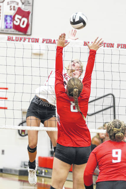 Bluffton's Taylor Schwab hits a spike against Pandora-Gilboa's Kendall Hovest during Thursday night's match at Bluffton.
