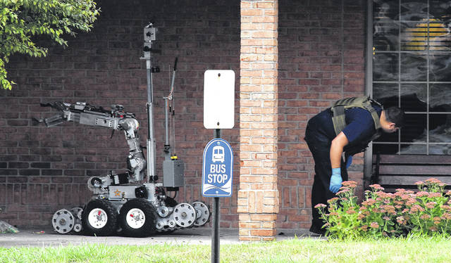 A bomb squad member checks under a bench at Bob Evans, 1810 Harding Highway, Lima, after removing and detonating a suspicious package with the bomb squad robot Monday morning.