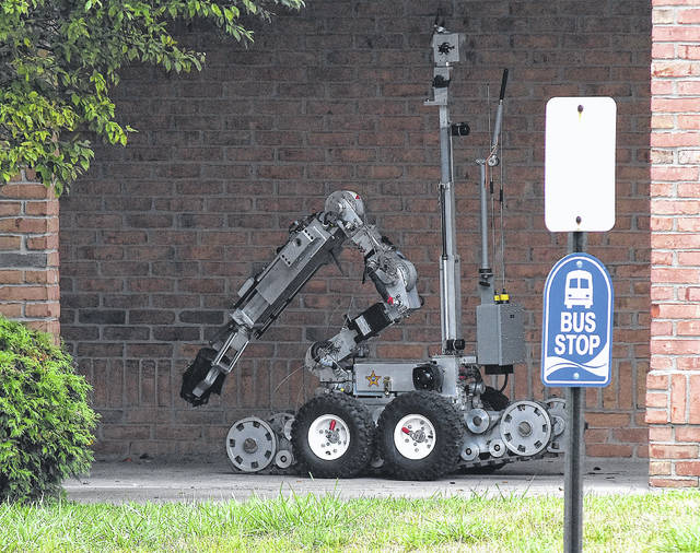 The bomb squad robot removes a suspicious package under a bench at Bob Evans, 1810 Harding Highway, Lima, on Monday morning.