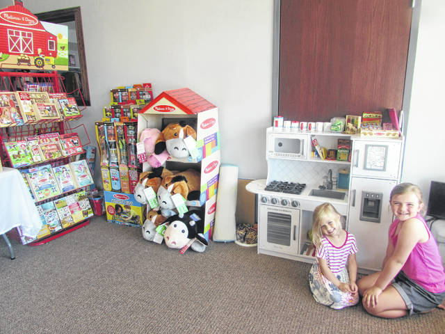 From left are Quinn Schroeder, 3, and her sister, Katem, 8, playing in a children's area at their mother's store, The Olive Tree Boutique.
