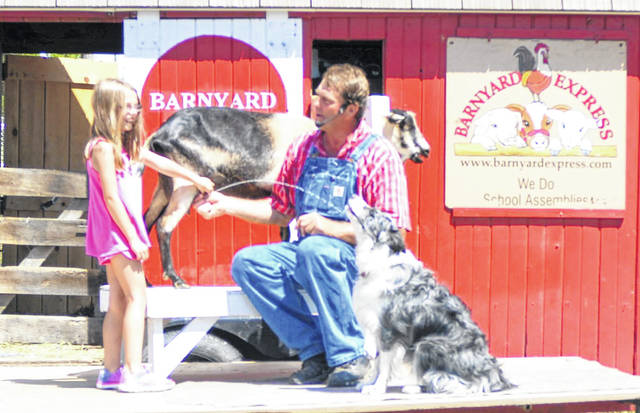 John Forshee and Ella Owsley, 8, hydrate Bunch the dog with the help of Goofy the goat.