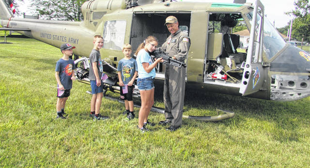 John Walker, president and CEO of American Huey 369, shows a Huey helicopter and M-60 machine gun used in Vietnam to from left Graeme Gasser, of Fort Jennings, Mason and Austin Utrup, both of Chesterfield, Michigan, and Evie Gasser, of Fort Jennings.