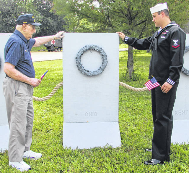From left are World War II and D-Day Navy Veteran Ray Woods, of Leipsic, and Austin Kehres, of Fort Jennings, who currently is serving in the Navy, sharing a moment at the traveling World War II memorial during Fort Fest in Fort Jennings Friday.