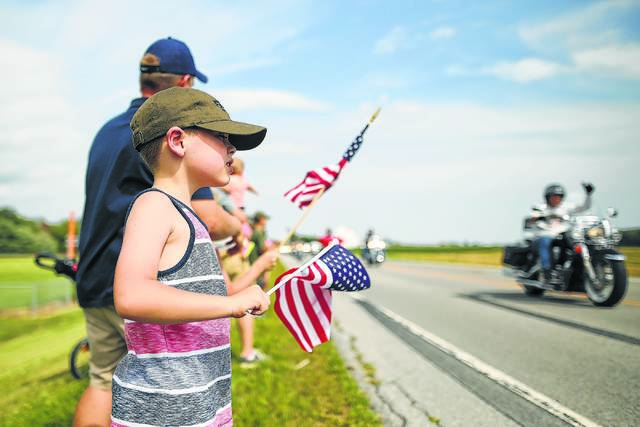 Six year-old Owen Dickman, of Dublin, waves a flag as he watches helicopters and motorcylces escort the military displays during the kick off to the Fort Fest last year