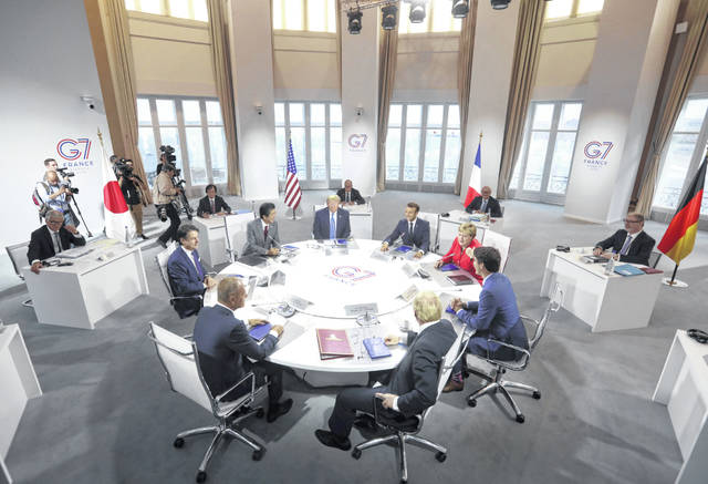 World Leaders prepare to start a working session on World Economy and Trade on the second day of the G-7 summit in Biarritz, France Sunday. They are from clockwork top center: President Donald Trump, French President Emmanuel Macron, German Chancellor Angela Merkel, Canadian Prime Minister Justin Trudeau, Britain's Prime Minister Boris Johnson, President of the European Council Donald Tusk, Italian Premier Giuseppe Conte and Japanese Prime Minister Shinzo Abe. (AP Photo/Markus Schreiber)
