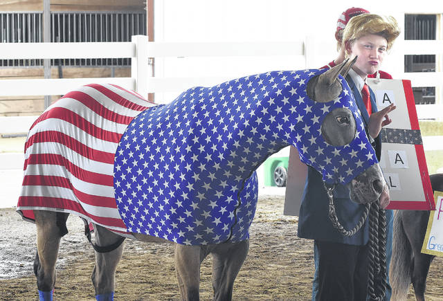 Dawson Clay, 13, is dressed as President Trump with his horse named Trumpet during the Allen County Fair Junior. Fair Horse & Pony Costume Class on Thursday.
