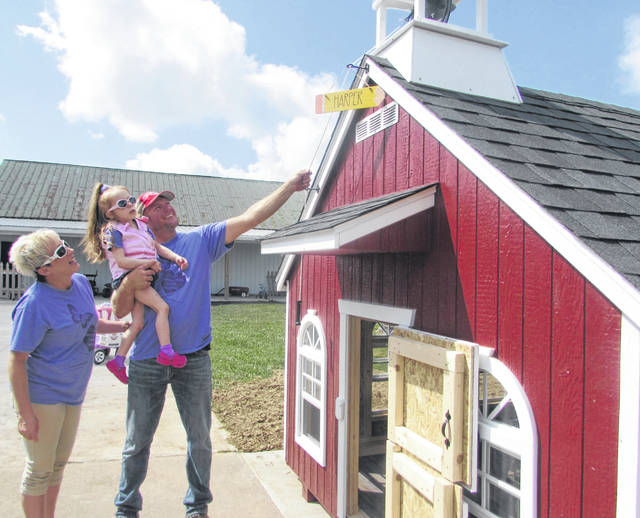 Harper Huelskamp, 5, who has an epilepsy disorder, checks out a schoolhouse with her mother Carrie and father Matt that was donated to her by Make A Wish Foundation Wednesday.