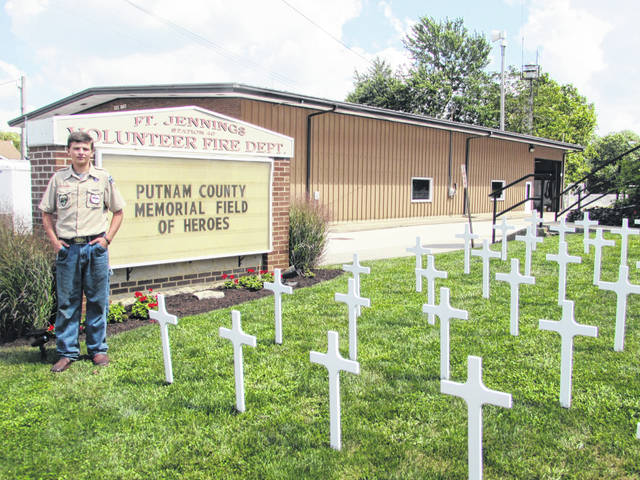 Pictured is Fort Jennings Boy Scout Austin Ricker standing next to his Memorial Field of Heroes travelling exhibit outside of Jennings Memorial Hall.