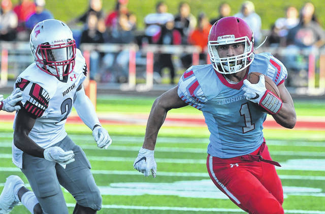 Lima Central Catholic's Rossy Moore runs for yardage against Lima Senior during Thursday night's Crosstown Gridiron Classic against Lima Senior at Spartan Stadium.