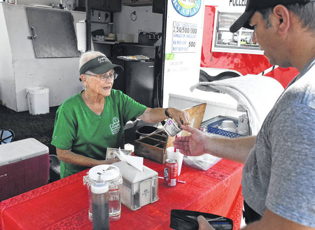 Dorthy Lugibihl, 85, of Lugibihl's Home Made Ice Cream of Bluffton, sells a Big Red ice cream float to Rob Tudor, of Columbus Grove, on Tuesday. The Lugibihls have been making and selling ice cream at the fair for 30 years.