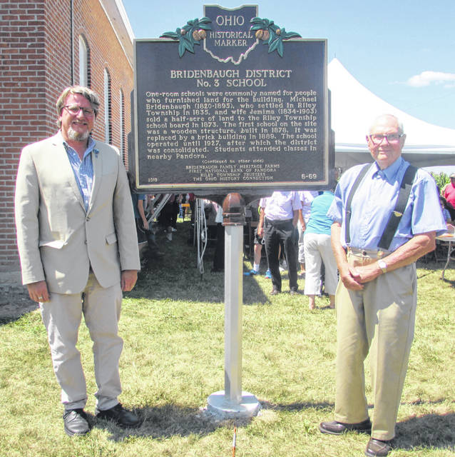 From left are Andrew Verhoff, team lead Local History Services, Ohio History Connection, with Dale Bridenbaugh, who owns and restored the Bridenbaugh One-Room Schoolhouse in Pandora, standing next to a historical marker placed at the site Friday.