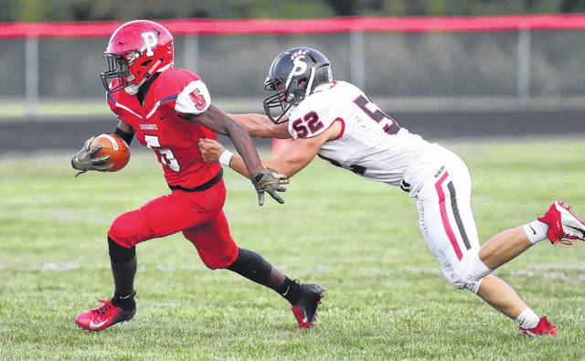 Perry's Terry Riley looks for more yardage as Spencerville's Jackson Goecke attempts to sure the tackle during Friday night's game at Perry.