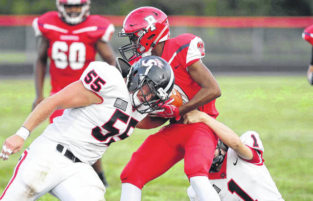 Spencerville's Eli Yahl (55) and Tyler Koenig work to bring down Perry's Jaquarius Austin during Friday night's game at Perry.