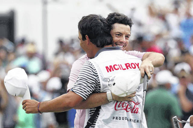 Rory McIlroy, right, hugs his caddy after winning the Tour Championship golf tournament and The FedEx Cup Sunday, Aug. 25, 2019, at East Lake Golf Club in Atlanta. (AP Photo/John Bazemore)