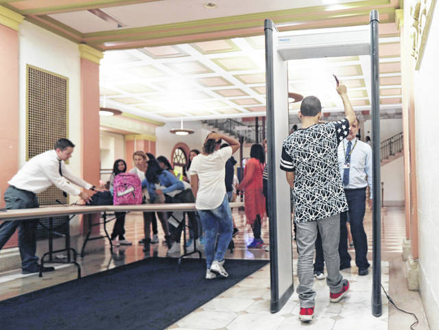 """In this Sept. 6, 2016, photo, students at William Hackett Middle School pass through metal detectors on the first day of school in Albany, N.Y. Schools around the country have been setting up teams to assess threats posed by students who display signs of violence like the former student who compiled a """"hit list"""" years ago in high school and went on to kill nine people in a weekend shooting in Dayton, Ohio. (AP Photo/Mike Groll)"""