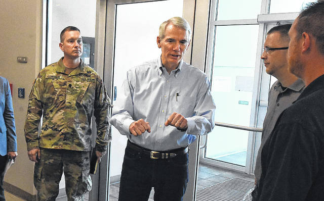Senator Rob Portman (R-OH) speaks with officials and union members after a visit to Joint Systems Manufacturing Center in Lima on Thursday morning.