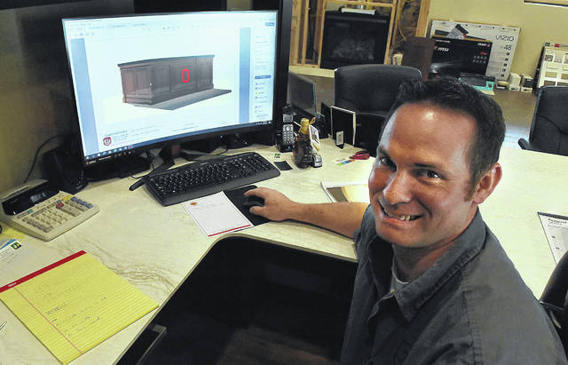 Tyson Bowman shows a computer drawing of Ohio State football coach Ryan Day's maple desk. It is being constructed at Bowman's Fine Cabinetry on North Cable Road in American Township.