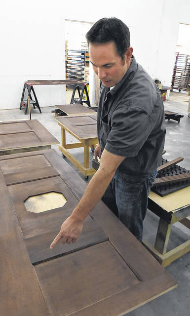 Tyson Bowman points to area's for inlay in Ohio State football coach Ryan Day's new desk.