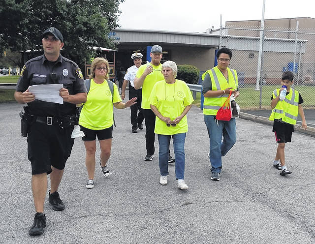Lima Police officer Chad Kunkleman leads the way for Tuesday night's Citizens Walking the Beat event.