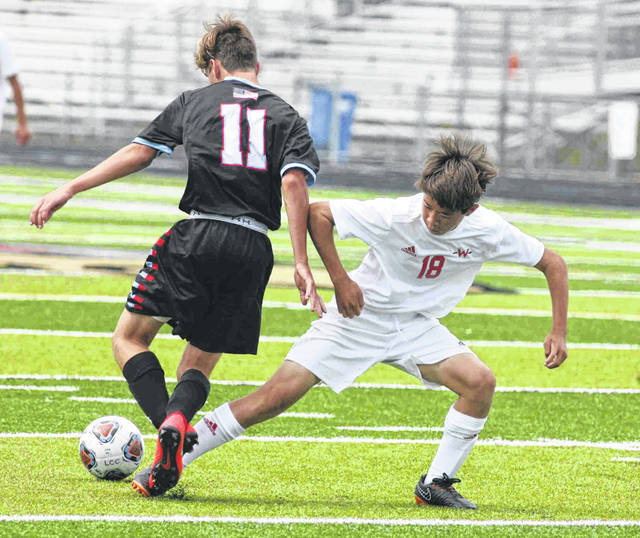 Wapakoneta's Aiden Schneider looks to disrupt the run of Lima Central Catholic's Connor Latham in the season opener for the two teams at Spartan Stadium Saturday.