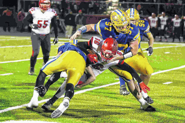 Van Wert's Jake Hilleary is tackled. by St. Mary's Braeden Dunlap and Blake Kanorr (97) during the Division IV Regional Semifinal at Spartan Stadium in Lima on Friday night.    Levi A. Morman | The Lima News