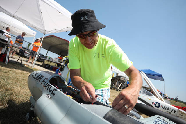 Event chairman Ben Burden, of Harrod, refuels and tends to his T-33 airplane during the annual Lima Area Radio Kontrol Society's Big Bird Fly-in on Saturday afternoon.