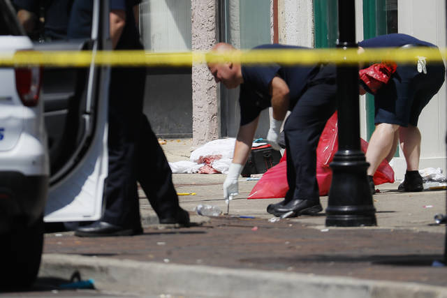 Authorities remove bloody rags and debris at the scene of a mass shooting, Sunday, Aug. 4, 2019, in Dayton, Ohio. Multiple people in Ohio have been killed in the second mass shooting in the U.S. in less than 24 hours, and the suspected shooter is also deceased, police said.