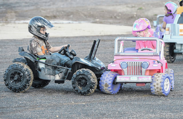 Bluffton's Gunnar Brenneman, 10, left, and Lima's Elleah McClure, 4, compete in Monday's Kids Power Wheels Derby at the Allen County Fair.