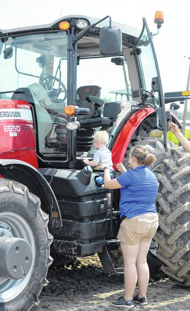 Jessica VanDenbroek and Henrik, 22 months, climb into a Massey Ferguson tractor during Sunday's Dream Day at The Allen County Fair.