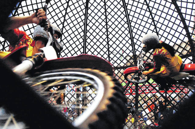 "Ricardo Flores, left, looks across the ""sphere of death"" at wife Arcelia, right, as they ride motorcycles in circles around one another in front of a large crowd."