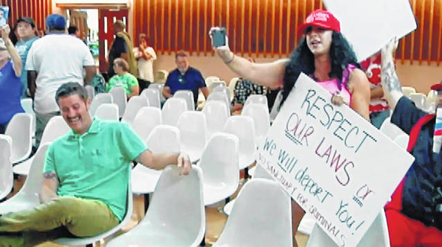 "This photo from video provided by KVOA-TV shows Alex Kack, in the green shirt at left, laughing at a protester during a vote to put a ""sanctuary city"" initiative on the November ballot during a meeting of the Tucson, Ariz., City Council Tuesday, Aug. 6. Kack is mystified that video of him simply laughing at the meeting has captivated the internet. Kack, also known as ""#GreenShirtGuy,"" told The Associated Press on Thursday that social media reaction spawned by a news clip of him shaking with laughter at a Tucson City Council meeting has been ""surreal."""