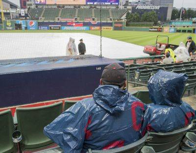 Indians fans wait out a rain delay before a Tuesday night scheduled game against Texas in Cleveland. The game was eventually called. (AP photo)