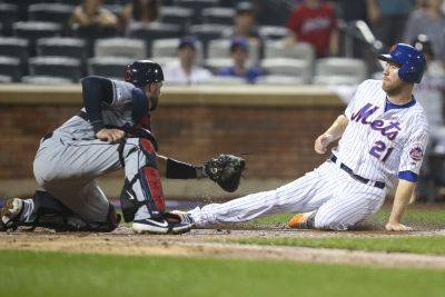 Cleveland's Kevin Plaweckiout tags out the Mets' Todd Frazier during Thursday night's game in New York. (AP photo)