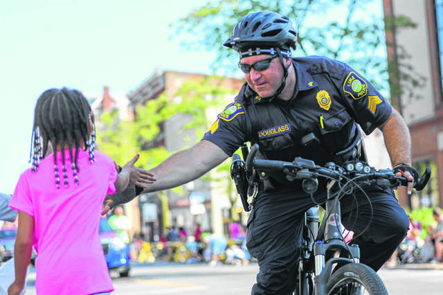 Officer Matt Douglass gives a five to Aria Butler of Lima during the Labor Day Parade held downtown last year.