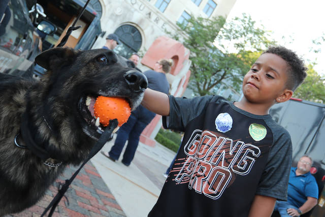 Six-year-old Ky-air Kitchen, of Lima, pets L-9 officer Fanto during the downtown National Night Out on Tuesday evening.