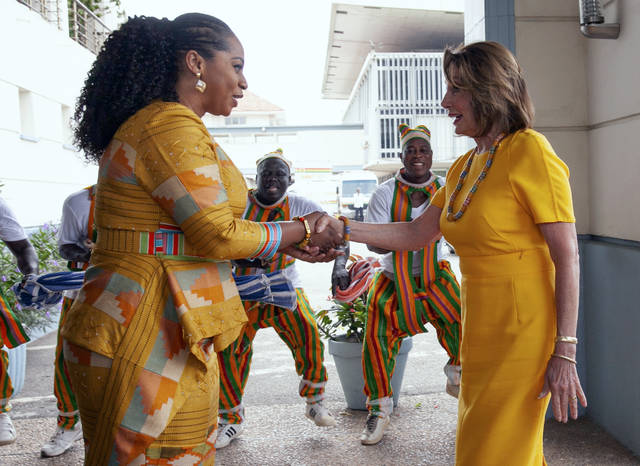 FILE - In this Wednesday, July 31, 2019 file photo, U.S. House Speaker Rep. Nancy Pelosi, D-Calif., shakes hands with the Hon. Sarah Adwoa Sarfo outside Ghana's Parliament in Accra, Ghana, during a visit by a U.S. congressional delegation. On Friday, Aug. 2, 2019, The Associated Press reported on photos circulating online, made during this visit, incorrectly asserting that the House Democrats were vacationing in Venice, Italy. The diplomatic trip was made by U.S. legislators to mark the 400th anniversary of the slave trade.