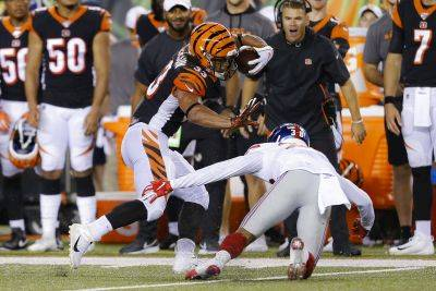 Bengals running back Rodney Anderson tries to avoid New York Giants cornerback Henre' Toliver during Thursday night's preseason game in Cincinnati. (AP photo)
